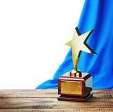 Star la tavola di legno del premio e sui precedenti della tenda blu Fotografia Stock Libera da Diritti