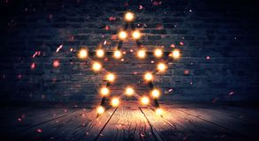 Star lamp on the background of an old brick wall, on the wooden floor, lights, lights, lights, glare, smoke. Exhibition star, light object, interior decor stock photos