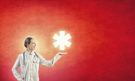 Star of life. Young female doctor holding medicine symbol in hands stock photo