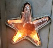 Star light. A metal candle holder with cutout glass star Royalty Free Stock Images
