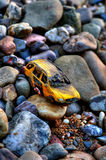 Star Oil Toy Car in Rocks. Old damaged toy car in rocks Stock Photography