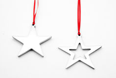 Star Ornaments. Shiny, silver star ornaments with red ribbons on a white background Stock Image