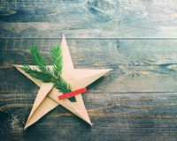 Star from paper and a fir-tree branch on a wooden old rough surface Royalty Free Stock Photography