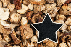 Star, pointer, price, tag, lies on dried mushrooms Royalty Free Stock Images
