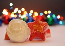 Star and rose soaps. White and red soaps in shape of a star and rose with golden details,christmas light in background Royalty Free Stock Image