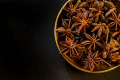 Star shape anis seeds in bowl on black slate. Background Stock Photos