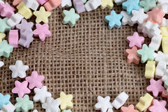 Star shape candy on burlap background texture Royalty Free Stock Photo