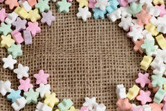 Star shape candy on burlap background texture. Stock Photo