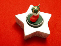 Star shape Christmas decoration on red tablecloth. Closeup photo of a nice star shape Christmas decoration with a green candle and red boots on it put on a red stock images