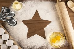 Star shape made with cooking flour on a wooden table. Royalty Free Stock Photography