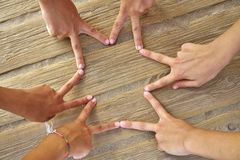 Star shape with six hand fingers on a beach. Wood Royalty Free Stock Photography