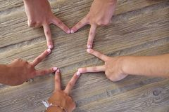 Star shape with six hand fingers on a beach. Wood Stock Image