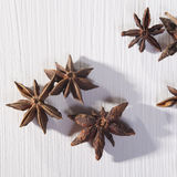 Star shaped anise seeds on a white wooden background Royalty Free Stock Image