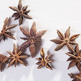 Star shaped anise seeds on a white wooden background Stock Photos