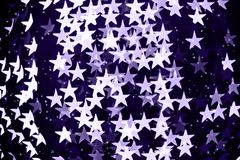 Star shaped blurred bokeh background with sparkles. Ultra violet Stock Image