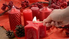 Star-shaped candle is lit. Besides Christmas decoration. Red Star-shaped candle is lit. Besides Christmas decoration stock video