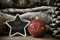 Star-shaped chalkboard with the text happy holidays. A star-shaped chalkboard with the text happy holidays surrounded by christmas balls and natural ornaments Royalty Free Stock Photography
