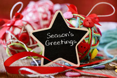 Star-shaped chalkboard with the text seasons greetings Royalty Free Stock Image
