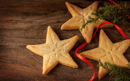Star shaped christmas cookies and pine tree branch on wood Stock Photo