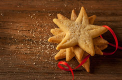 Star shaped christmas cookies and red ribbon on vintage wood Royalty Free Stock Photography