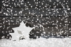 Star shaped christmas decoration christmas bulbs cinnamon stars on pile of snow against wooden wall snow is falling Royalty Free Stock Images