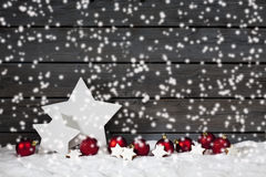 Star shaped christmas decoration christmas bulbs cinnamon stars on pile of snow against wooden wall snow is falling Royalty Free Stock Photo