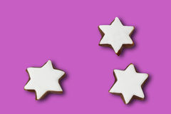 Star shaped christmas pastries purple on background Stock Images