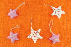 Star shaped Christmas tree decorations on orange hessian. New Year toy stock image