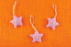 Star shaped Christmas tree decorations on orange hessian. New Year toy royalty free stock photo