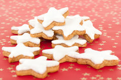 Star shaped cinnamon biscuits on red background with golden stars Stock Photos