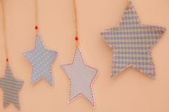 Star shaped cloth patches hanging on the wall.  Royalty Free Stock Photo