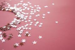 Star-shaped confettien die op een roze achtergrond worden verspreid Viering en partij, concept De ruimte van het exemplaar royalty-vrije stock foto