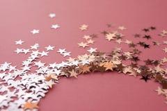 Star-shaped confettien die op een roze achtergrond worden verspreid Viering en partij, concept De ruimte van het exemplaar stock foto's