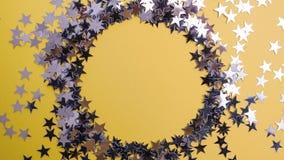 Star-shaped confettien op een gele achtergrond worden verspreid die Viering en partij, concept De ruimte van het exemplaar royalty-vrije stock afbeeldingen