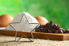 Star-Shaped Cookie Cutter. With baking ingredients such as wheat flour, chocolate chips and eggs in the back (Selective Focus, Focus on the cookie cutter Royalty Free Stock Images
