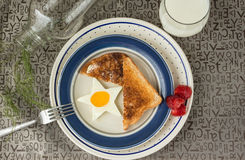 Star shaped fried egg and toast with strawberries on the side sitting in a white plate with a blue rim Royalty Free Stock Photography
