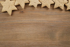 Star shaped gingerbread cookies on wooden background border Royalty Free Stock Image