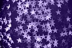Star shaped blurred bokeh background with sparkles. Ultra violet Royalty Free Stock Images