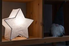 A star-shaped night lamp glows on a shelf