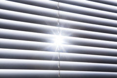Star Shaped Sunburst Shines Through Closed White Window Blinds Stock Image