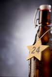 Star shaped tag with 24 December number around bottle Stock Photos
