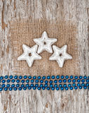 Star shapes, burlap textile and chaplet. On the old wood background royalty free stock photography