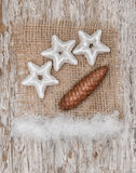 Star shapes, burlap textile and pinecone. On the old wood background royalty free stock images