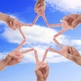 Star in the sky. A star made out of fingers from different people with the sky as background Royalty Free Stock Image