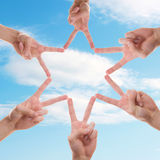 Star in the sky. A star made out of fingers from different people with the sky as background Stock Photography