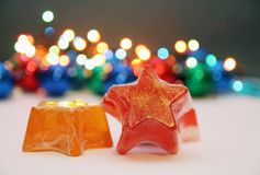Star soaps. Orange and red soaps in shape of a star with golden details,christmas light in background Stock Photo