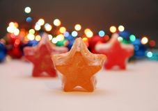 Star soaps. Orange and red soaps in shape of a star with golden details,christmas light in background Royalty Free Stock Photos