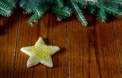 Star sugar cookie with room for text. Yellow star sugar cookie with roomm for text on a wood table with evergreen border Royalty Free Stock Image