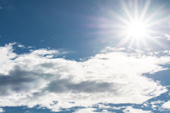 Star of sun in blue sky with white clouds Stock Images