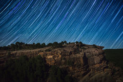 Star trail above rock cliff Royalty Free Stock Photos